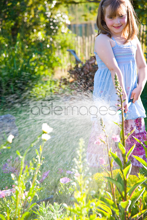 Young Girl Watering Flowers with Garden Hose