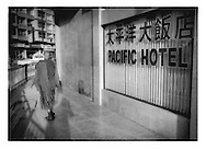 Buddhist monk walks past sign written in Chinese characters and English alphabet, not Burmese script, for hotel across from Mandalay train station, Burma (Myanmar).