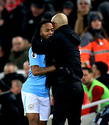 Manchester City manager Pep Guardiola (right) with Manchester City's Raheem Sterling (left) after he is substituted off during the Premier League match at Anfield, Liverpool.