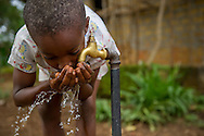 A young boy drinks from an outdoor spigot in the Grafton neighborhood of Freetown, Sierra Leone. Plumbing and housing in the area are being rebuilt after the country's civil war.