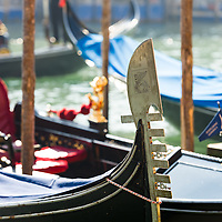 a gondolier is seen standing in defocused silhouette with the iconic gondola prow shown in detail in the forgeround