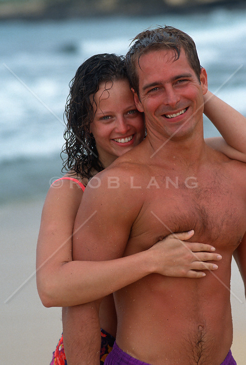 woman and man at the beach smiling while looking at the camera
