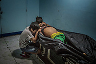 Ginnalyn Soriano, 21, and her youngest brother, Jonas bid a final farewell to elder brother, Julius, 24 years old, whose corpse showed signs that his hands had been bound before he was shot to death during a police operation in Caloocan, Metro Manila. Philippines