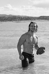 sexy man with a football in a lake