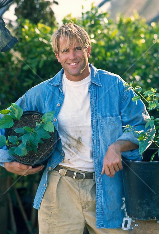 Blond man in a nursery holding plants
