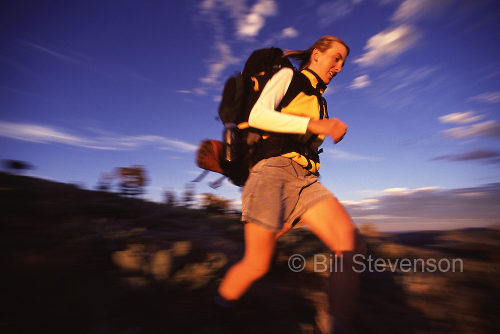 A motion blurred photo of a woman hiking fast at sunset in the Sierra mountains of California.