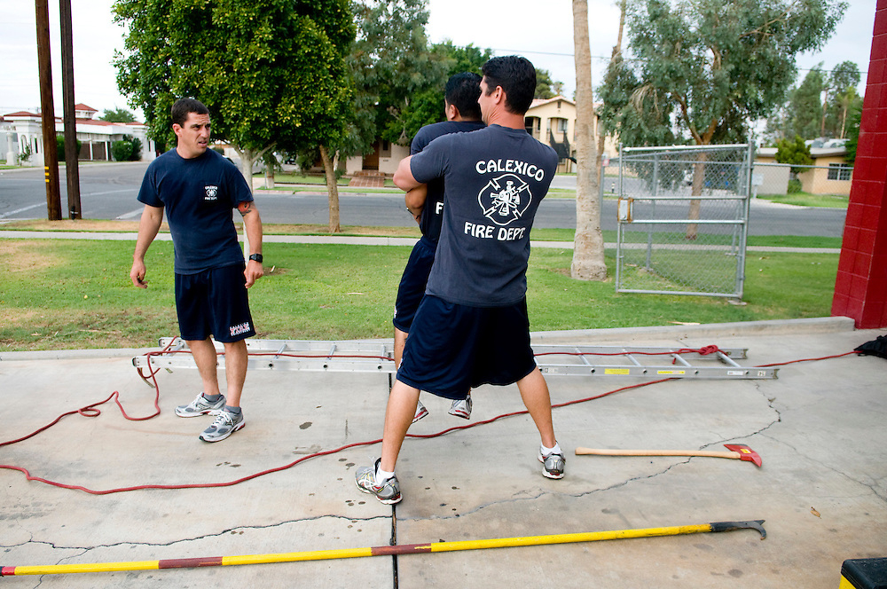 Firefighter Eddie Ainza messes around with Firefighter Geovanni Raygosa and Firefighter Brandon Bowers (left) at the Calexico Fire Department in Calexico, California, U.S. on Tuesday, July 31, 2012.