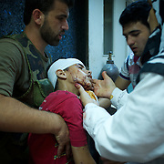 August 10, 2012 - Aleppo, Syria: People give assistance to a child, injured minutes earlier by heavy shelling from the Syrian Army against a bakery in the residential area of Tariq Al-Bab in central Aleppo. At least 12 people have died and more the 20 got injured during the attack...The Syrian Army have in the past week increased their attacks on residential neighborhoods where Free Syria Army rebel fights have their positions in Syria's commercial capital, Aleppo. (Paulo Nunes dos Santos/Polaris)