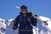 SHOT 3/12/10 12:46:59 PM - A skiier carries his skis while hiking the ridgeline at Silverton Mountain in Silverton, Co. Silverton Mountain is unique amongst ski resorts requiring a guide (most of the season), avalanche gear and limiting the number of daily visitors. There are multiple bowls, chutes, cliffs and natural terrain features to be discovered during a visit to Silverton Mountain. It is the highest Ski Area in North America with a peak of 13,487' and it is also the steepest with no easy way down. The mountain is left in it's natural state with the exception of the avalanche reduction work which occurs. There is only one chair at the mountain though most skiiers and snowboarders will end up hiking in various directions at the top. The mountain also features heliskiing trips for $159 a trip (at the time of visit). The mountain opened in 2002. (Photo by Marc Piscotty / © 2010)