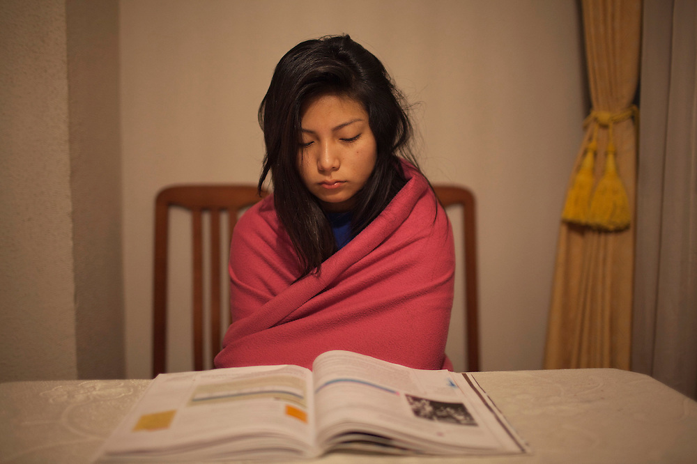 Pie de foto: Abigail se ha levantado a las 5 am  para poder repasar lo estudiado para un examen de historia. <br /><br />Titulo: Aby<br /><br />Un semblante serio la acompa&ntilde;a desde que se despierta. Todos los d&iacute;as, a las seis de la ma&ntilde;ana, empieza la jornada para Abigail (18 a&ntilde;os).<br /><br />Sus progenitores, aunque separados hace 11 a&ntilde;os, decidieron cambiar un d&iacute;a su Chile originario por Espa&ntilde;a, como muchos otros inmigrantes, en busca de una mejor posici&oacute;n econ&oacute;mica. La madre lleg&oacute; en 2001 y, un a&ntilde;o despu&eacute;s, el padre. En 2005, vinieron los cuatro hijos &ndash;Abigail, la mayor de la prole- para vivir junto a ella.<br /><br />Moradora de Aluche, un barrio del sur de Madrid que, como muchos otros perif&eacute;ricos de la capital espa&ntilde;ola, vio mudar su fisionom&iacute;a en los &uacute;ltimos a&ntilde;os a ra&iacute;z de la llegada de numerosa poblaci&oacute;n extranjera, Abigail preferir&iacute;a regresar a su Arica natal lo antes posible.<br /><br />Discreta, silenciosa e introvertida, esta joven chilena no ha conseguido<br />amistades espa&ntilde;olas y suele relacionarse con adolescentes de Rumania y de otros pa&iacute;ses latinoamericanos diferentes al suyo, principalmente Ecuador y Colombia.<br /><br />Tiene una ferrea formaci&oacute;n religiosa pero sin duda su lugar m&aacute;s sagrado es el locutorio, donde puede conectarse &ndash;v&iacute;a telef&oacute;nica, v&iacute;a Internet- con todo eso que tanto extra&ntilde;a, su gente de Chile, todos esos amigos y familiares que quedaron all&aacute; y con quienes Abigail desea reunirse m&aacute;s pronto que tarde.<br /><br />Abigail estudia Cosm&eacute;tica en un instituto del barrio de Chamber&iacute;, uno de los m&aacute;s tradicionales de Madrid.