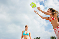 Teenage girls (16-17) playing beach volleyball low angle view