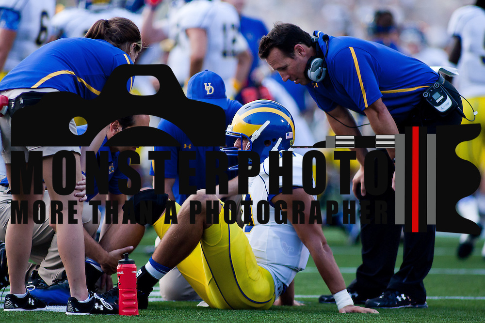 Delaware training staff and Head Coach K.C. Keeler assessing Delaware Quarterback Trevor Sasek #13 knee after being injured after making a reception on a trick play in the third quarter Saturday Sept. 3, 2011 at Marine Corps Memorial Stadium in Annapolis Maryland.<br /> <br /> Navy would go on to defeat Delaware 40-17 Navy leads the all-time series against the Blue Hens, 9-7, including a 35-18 victory in 2009 when quarterback Ricky Dobbs rushed for five touchdowns.  <br /> <br /> Navy will hit road for a show down with Western Kentucky next Saturday Sept. 10, 2011 in Bowling Green, Ky.