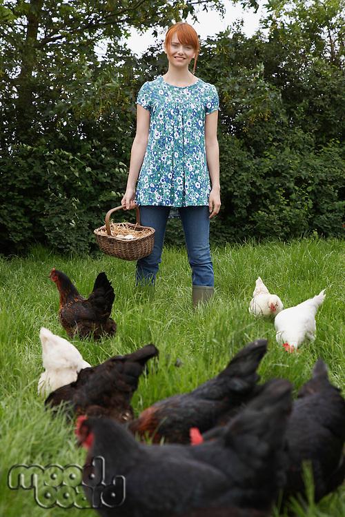 Woman holding egg basket by hens in garden portrait