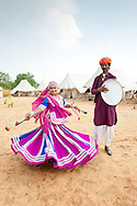 Indian girl dances to the beat of a tambourine at tented encampment at Pushkar Fair