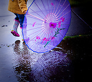 A young African American girl with umbrella and bright yellow coat splashing in a rain puddle.