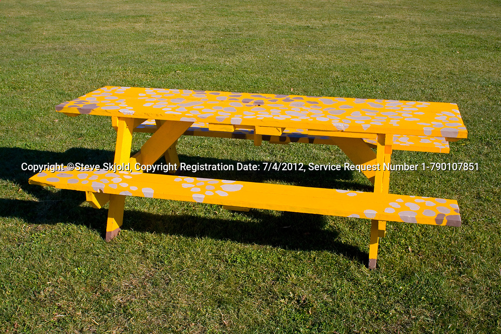 Bright yellow picnic table covered with splotches of white or sliver paint. Franconia Sculpture Park Franconia Minnesota MN USA