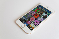 Gold and white Apple iPhone 6 with an Instagram photo feed against a white background