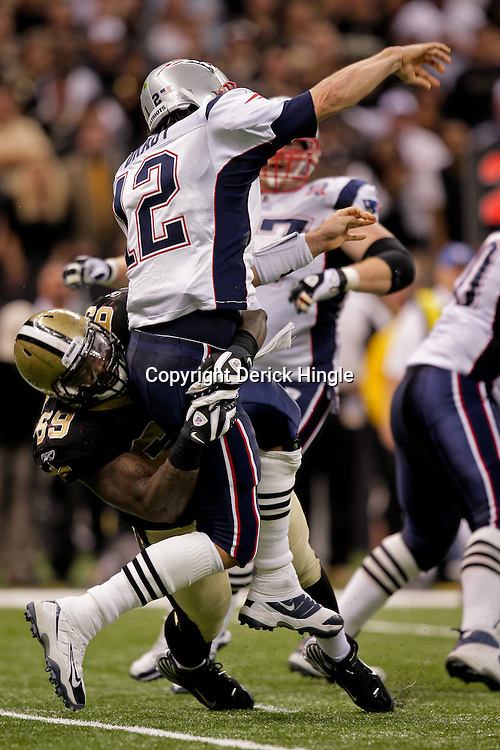 2009 November 30: New Orleans Saints defensive end Anthony Hargrove (69) hits New England Patriots quarterback Tom Brady (12) as he throws during a 38-17 win by the New Orleans Saints over the New England Patriots at the Louisiana Superdome in New Orleans, Louisiana.