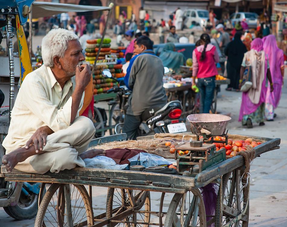 Man sat on food cart at local market (India)