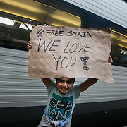 A young boy greets refugees arriving at the station from Syria. Help point at Copenhagen Central Station. An unprecedented number of refugees arrived from Germany in early September, most being Syrian war refugees, some from Afghanistan. Most wanted to travel on to Sweden and a number of Danish citizens created a spontanious network to assist the refugees with travel, food, clothes and psycological support.