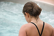 A young girl watches the swirling water while standing in a hot tub.