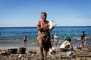 Old women bring her meat part, Residents in the lamalera village, Indonesia cathing  sperm whales with traditional method to provide meals for the entire village and part of the Lembata island where the village is located..