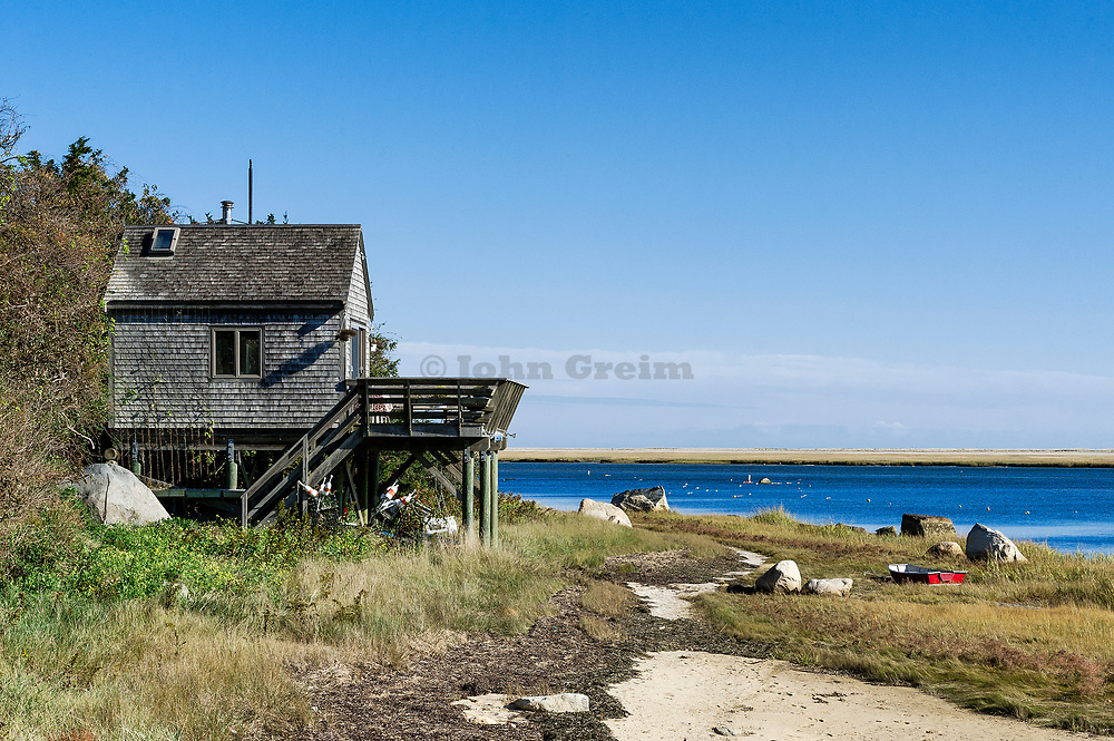 Quaint beach cottage on stilts with rowboat along Weeset Point, Nauset Harbor, Cape Cod, Massachusetts, USA.