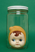 doll head in glass jar