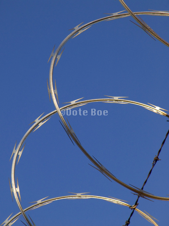 close up of new razor wire strengthened with barbed wire