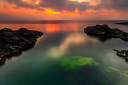 Green rock in the sea at sunrise