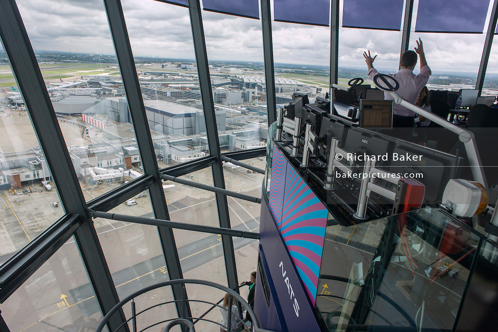 Aerial view (through control tower windows) showing NATS air traffic controllers and expanse of airport land at London Heathrow.