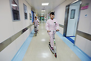 WUHAN, CHINA -  (CHINA OUT) <br /> <br /> Nurses Using Scooters To Get Around Hospital Quickly<br /> Nurses ride scooters running in the gallery of the Hubei Maternal and Child Health Hospital  in Wuhan, Hubei Province of China. Nurses using scooters to save time for faster work. <br /> ©Exclusivepix