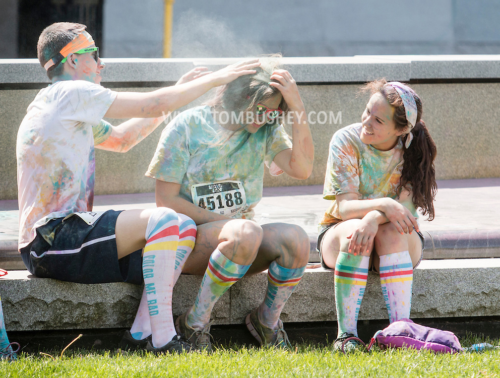 Scranton, Pa. - A boy rubs colorful powder out of a girl's hair after the Color Me Rad 5K color run on May 24, 2015.