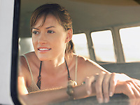 Woman in sitting in front seat of van head and shoulders view through window