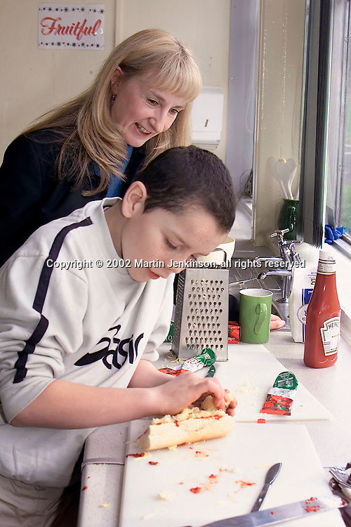 Teacher (Kath Stallard) watching as a boy prepares food ..© Martin Jenkinson, tel/fax 0114 258 6808 mobile 07831 189363 email martin@pressphotos.co.uk. Copyright Designs & Patents Act 1988, moral rights asserted credit required. No part of this photo to be stored, reproduced, manipulated or transmitted to third parties by any means without prior written permission