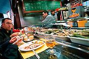Spanje, Barcelona, 10--1-2004..In de overdekte markt, boqueria, wordt in een tapabar de lunch gegeten. eetgewoonte, hapjes, horeca. ..Foto: Flip Franssen