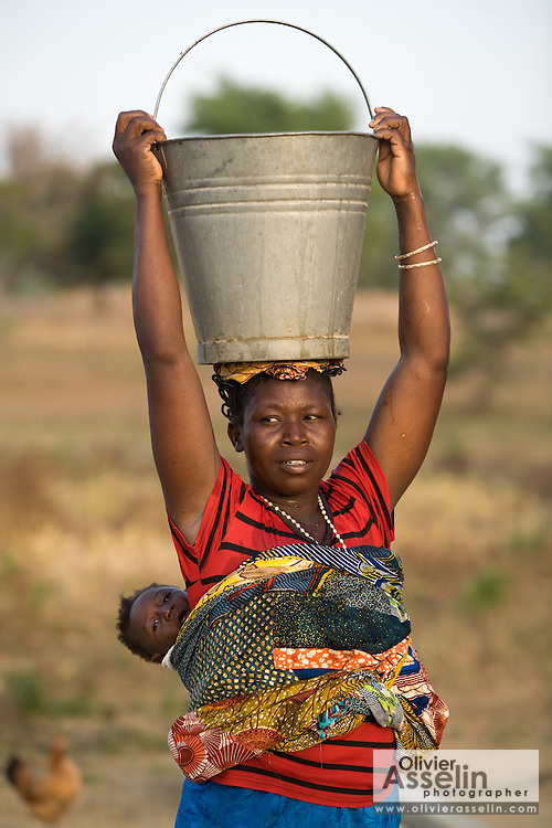 A woman carries a bucket of water atop her head and her child on her back.