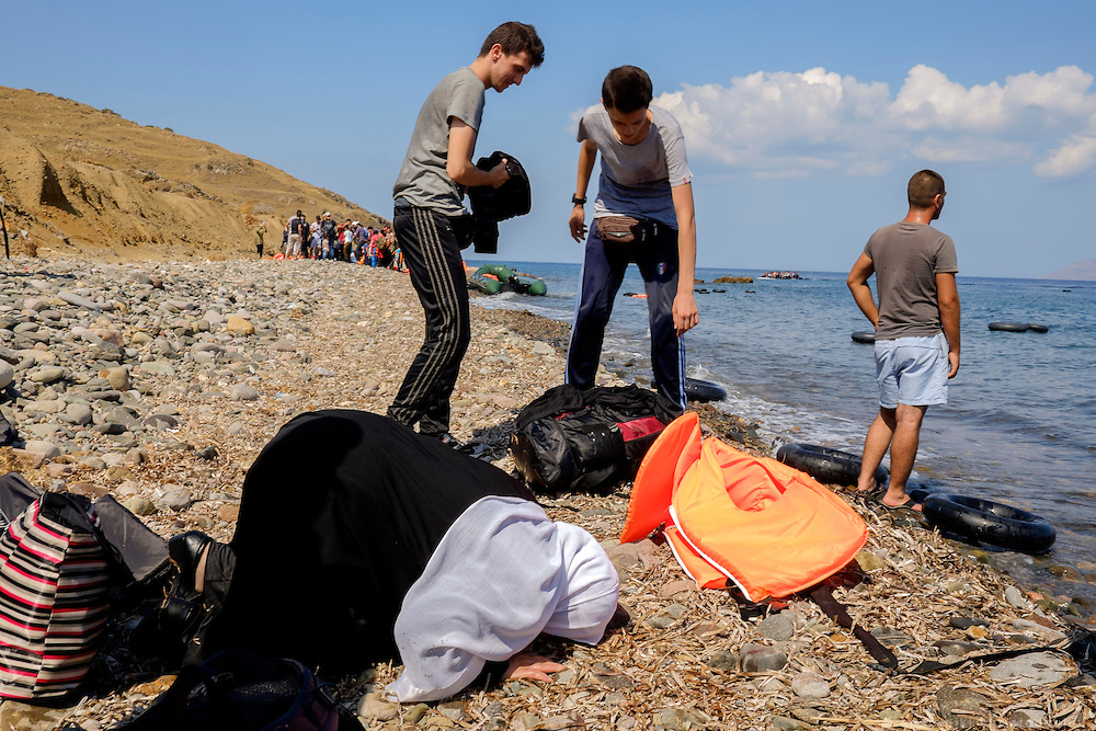 Refugee lady that just arived safely, praying to god. <br /> Refugees arriving on beaches near Molyvos village in Lesvos island. Thousands of them come from Turkey, crossing the sea border on inflatable dinghy boats, on a dangerous trip that has claimed many lives. Local people or NGOs expect them and help them in some places but after their arrival, most of them have to walk to the nearest village where they can hope for a places on busses that can take them to the city of Mytilene where they can register and eventually board on a ferry to Athens. Many decide to walk the distance as the busses aren&rsquo;t enough to accommodate the large number of people that arrive daily.