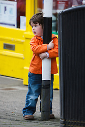 Young boy hanging on street pole, Westport, County Mayo, Ireland