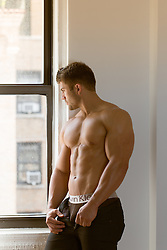muscular All American man without a shirt and open pants exposing his underwear by a window