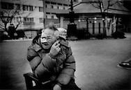 Battered homeless man smokes in a park near the Sumida River, Asakusa, Tokyo, Japan.
