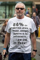 "© Licensed to London News Pictures . 16/09/2018. Manchester, UK. A man wearing a t-shirt that reads "" 86 percent of British Jews think Jeremy Corbyn is an antisemite...I am one of them "" . Thousands of people including the UK's Chief Rabbi and several Members of Parliament attend a demonstration against rising anti-Semitism in British politics and society , at Cathedral Gardens in Manchester City Centre . Photo credit : Joel Goodman/LNP"