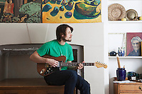 Young man sits in living room playing electric guitar