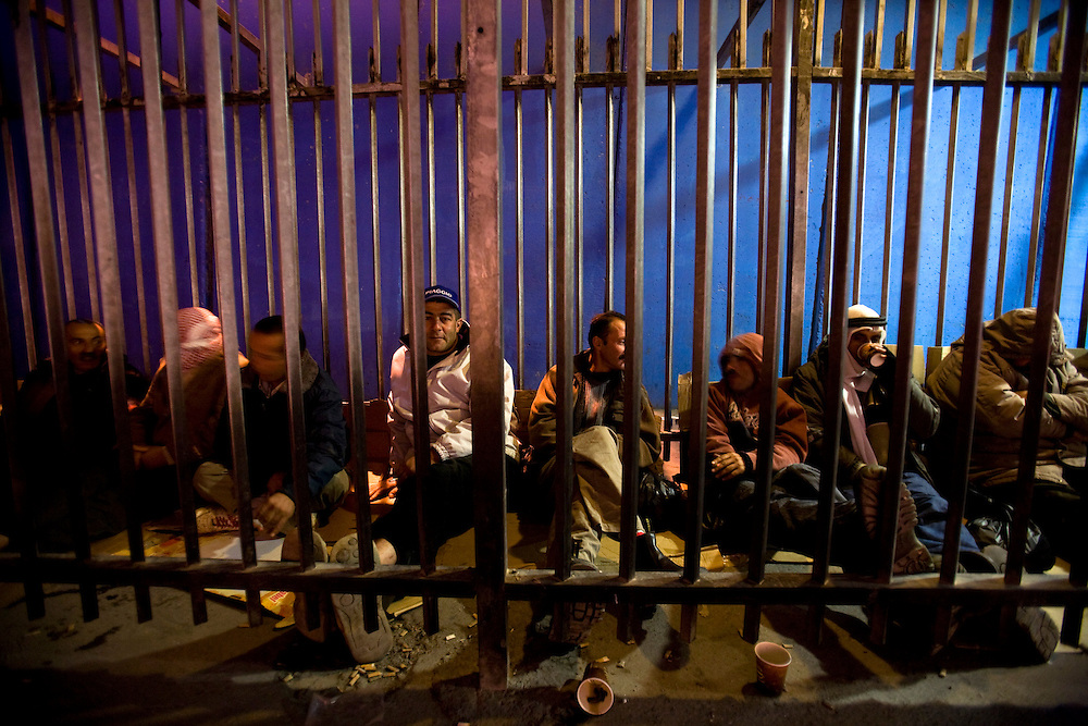 Bethleem, Palestinian Authority, Dec. 18. 2010...Palestinian workers queue along the separation wall at the checkpoint 300, the crossing passage between Bethleem and Jerusalem, on December 18. 2010 in Bethleem. Workers arrived every day at two o'clock in the morning  to catch a place at the entrance of the checkpoint, so they can arrived at time to their work in the Israeli side. Photo by Olivier Fitoussi