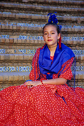 Europe, Spain, Andalucia, Sevilla (also known as Seville).  Girl in flamenco dress (11 years) on steps of Plaza de Espana (MR)