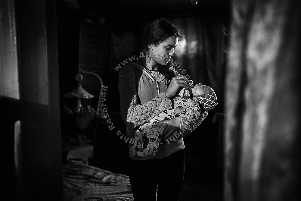 Ludmilla Palchick, 12, is holding her stepbrother of 18 months, Nikolas, while standing in a house that her family occupied in the town of Popasna, near the frontline in eastern Ukraine, after their own home was destroyed by a missile in 2014.