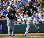 MESA, AZ - MARCH 6:  Carlos Quentin #20 celebrates with third base coach Jeff Cox #6 of the Chicago White Sox after hitting the first of 2 home runs against the Chicago Cubs on March 6, 2010 at HoHoKam Park in Mesa, Arizona. (Photo by Ron Vesely)
