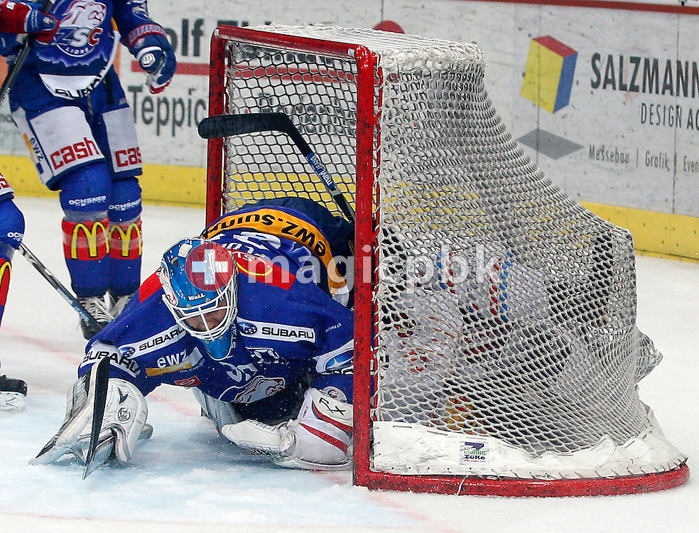 SC Bern forward Christoph Bertschy (bottom) slides in ZSC Lions goaltender Lukas Flueeler's goal after being tackled by ZSC Lions defender Mathias Seger (not pictured) during ice hockey game two of the Swiss National League A (Season 2011-2012) Playoff Final between ZSC Lions (ZSC) and SC Bern (SCB) held at the Hallenstadion in Zurich, Switzerland, Thursday, April 5, 2012. (Photo by Patrick B. Kraemer / MAGICPBK)