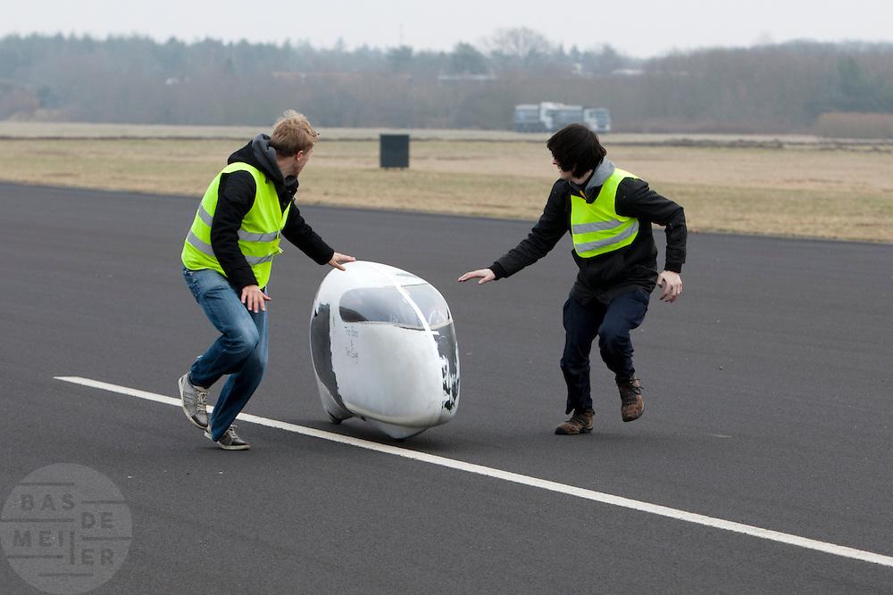 Een renner wordt opgevangen. Het Human Powered Team Delft (HPT Delft) houden op de voormalige vliegbasis Soesterberg testen om de renners te laten wennen aan het rijden in de Velox. Het team probeert het record Human Powered Vehicles te verbreken.<br /> <br /> Human Powered Team Delft (HPT Delft) is testing at the former airport Soesterberg to get the riders familiar with the bike and to train the stop and start.