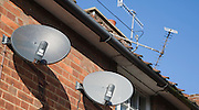 Old television aerials and modern satellite dish TV receivers on building